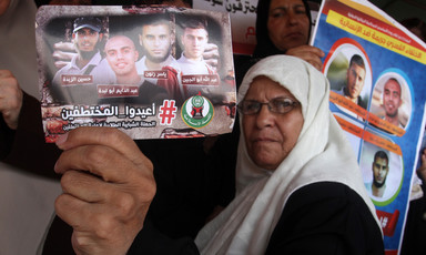 Woman in headscarf holds photo showing four men abducted in Egypt