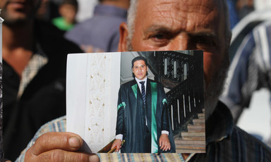Older man holds photograph of young man wearing graduation gown