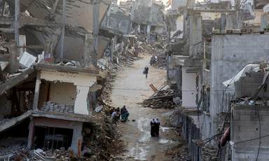 View of people walking through muddy road in between bombed-out buildings