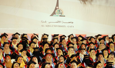 Women students wearing graduation caps and gowns sit in front of Al Aqsa University banner