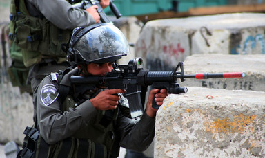 An Israeli Border Police officer aims a rifle from behind a concrete block