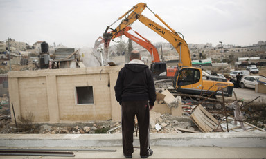 Man watches as heavy equipment is used to destroy home