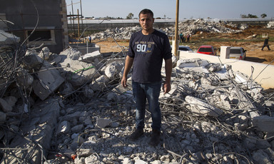 Young man stands on rubble of demolished home