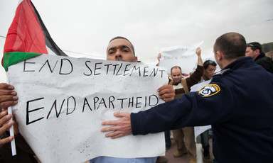 Israeli police officer places arm across Palestinian protester carrying sign reading End Settlements and Apartheid