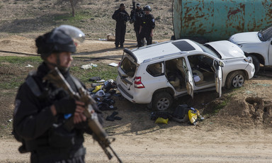 Militarized police officer holding rifle stands in foreground with SUV emptied of its contents in background