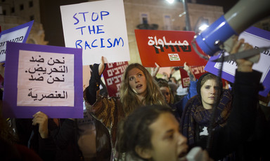 Protesters carry signs against racism