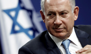 Close-up of Netanyahu with Israeli flag behind him