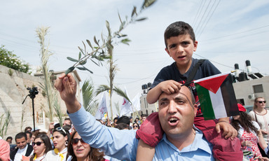 Man waving olive branch carries boy holding Palestine flag on his shoulders during Palm Sunday procession