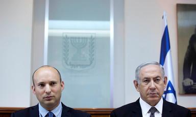 Naftali Bennett and Benjamin Netanyahu stand shoulder-to-shoulder in front of Israeli flag