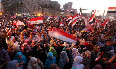 Crowd of hundreds of men and women wave Egyptian flags in public square