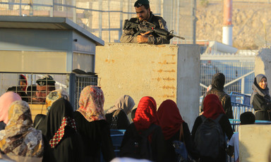 Palestinian woman walk through a checkpoint as an armed Israeli soldier is positioned above them