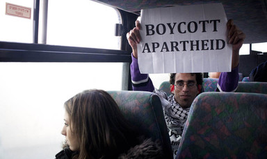 Bassel al-Araj sits on bus behind Israeli woman while holding up a sign reading Boycott Apartheid