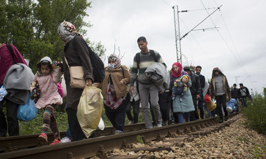 Men, women and children walk along railroad tracks while carrying their possessions