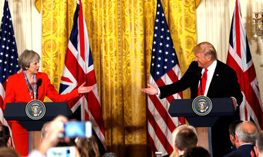 Theresa May and Donald Trump, standing at podiums during White House press conference, smile and reach their arms towards one another