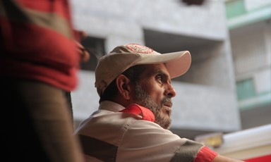 Profile of bearded man wearing paramedic's uniform and cap sitting in front of building