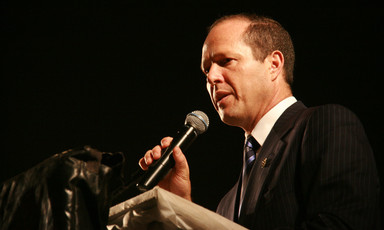 Close-up of Nir Barkat standing at a podium while holding a microphone to his mouth