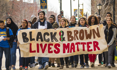 Racially diverse group of young people carry banner reading Black and Brown Lives Matter