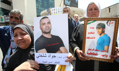 Women hold posters showing photos of men detained by Israel