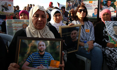 Women sitting on chairs hold photos of men being detained by Israel