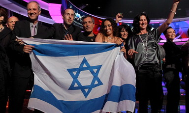 Group of people on Eurovision stage hold Israeli flag