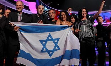 Group of people on Eurovision stage hold Israeli flag