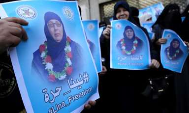Close-up of poster being held by women showing Lina al-Jarbouni wearing a garland of flowers around her neck