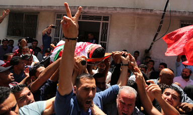 Man makes a V symbol with his right hand while Muhammad Bakr's shrouded body is carried on a stretcher in a crowd of people