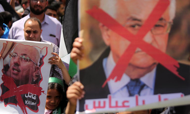 Protesters carry a large photo of Mahmoud Abbas with a red X across his face