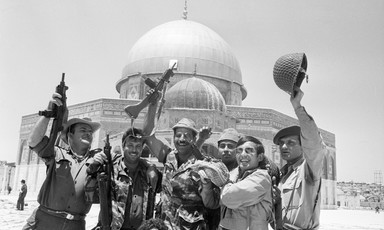 Soldiers seen from waist up raise rifles and helmets above their head while standing in front of Dome of the Rock