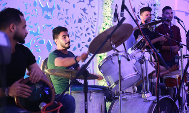 Close-up on young man playing on a drum kit with a tabla player and two singers standing on either side of him