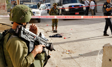 An Israeli soldier holding a rifle stands guard at a site marked by police tape