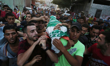 Youth wrapped in funeral shroud is carried on the shoulders of young men in crowded procession