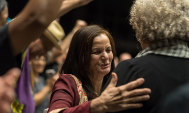 Rasmea Odeh, seen from chest up, puts a hand on the back of Angela Davis, seen from the back