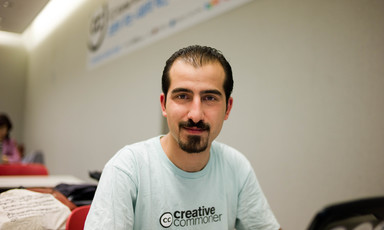 Smiling young man with goatee wearing Creative Commons t-shirt is seen from chest up