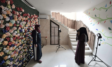 Woman wearing niqab takes a photo of a smiling woman standing in front of a wall decorated with paper flowers