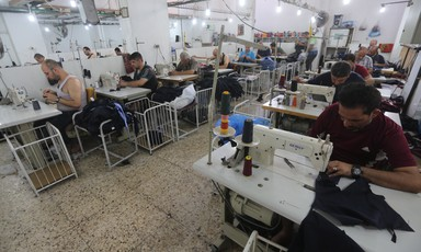 Photo shows men working at sewing machines in garment factory