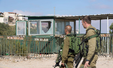 Two soldiers carrying heavy weaponry walk in front of checkpoint with shattered windows