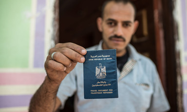 Man holds up passport-style document that says Arab Republic of Egypt Travel Document for Palestinian Refugees