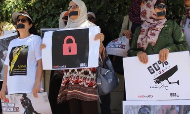 Photo of women with their mouths covered holding campaign signs condemning G4S and expressing solidarity to Palestinian hunger strikers.