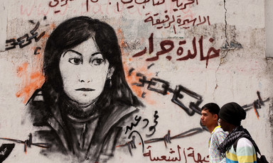 Two Palestinian children walk past a mural of Khalida Jarrar, a member of the Popular Front for the Liberation of Palestine, who remains jailed in Israeli prisons.