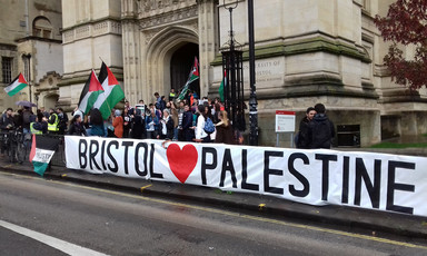 Long banner reading Bristol <3 Palestine is displayed by a crowd  waving Palestine flags outside a campus building