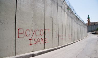 "Red graffiti on the Israeli apartheid wall dividing the East Jerusalem neighborhood Ras al-Amud from the West Bank town of Abu Dis reads, ""Boycott Israel"", on 26 March 2012."