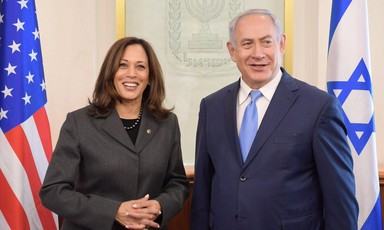 Smiling Kamala Harris stands next to Benjamin Netanyahu, also smiling, as the pair are flanked by American and Israeli flags
