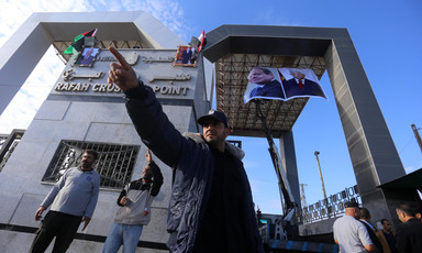 A Palestinian Authority officer raises an arm with a pointed index finger as he stands in front of Rafah crossing, decorated with posters of Mahmoud Abbas and Abdulfattah al-Sisi