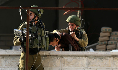 Two Israeli soldiers violently arresting a Palestinian boy.