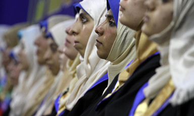 Photo shows row of young women wearing headscarves and graduation robes