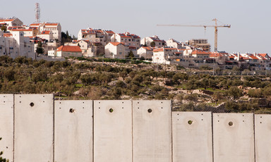 Landscape photo shows a construction crane is above a group of Israeli settlement homes with Israel's concrete wall in the foreground