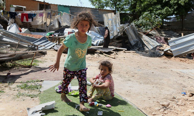 Two girls playing past the debris of homes after Israeli forces demolished them in Khan al-Ahmar.
