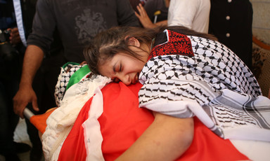 Sarah Shamasneh mourning over the body of her brother Muhammad Shamasneh during his funeral in Qatana