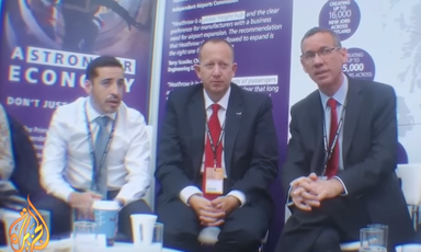 Three men with conference lanyards sit next to each other in a similar pose.